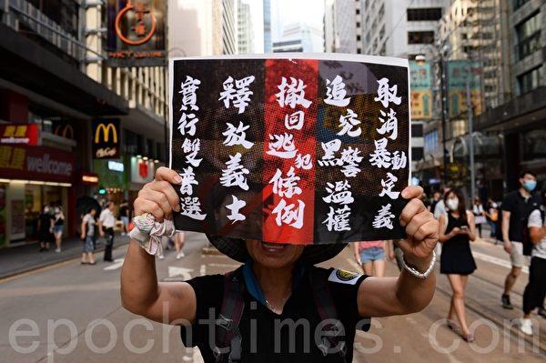 7月28日,遊行隊伍經過上環西港城,有市民舉起寫有五大訴求的海報。(宋碧龍/大紀元)