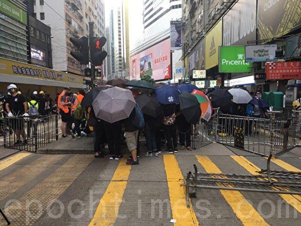 7月28日,有市民在怡和街用欄杆鐵馬等築起防線。(孫青天/大紀元)