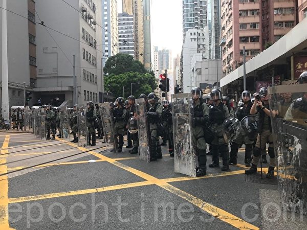 2019年7月28日,香港,中聯辦後門的德輔道西,防暴警察持長盾在西區警署門外排成一條直線橫跨整條馬路,防止有人接近中聯辦。(蔡雯文/大紀元)