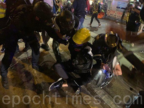 7月28日,警方速龍小隊也在8時突然衝前,警方並施放催淚彈,十多位示威者被暴力抓捕,雙手被索帶索緊。(李逸/大紀元)