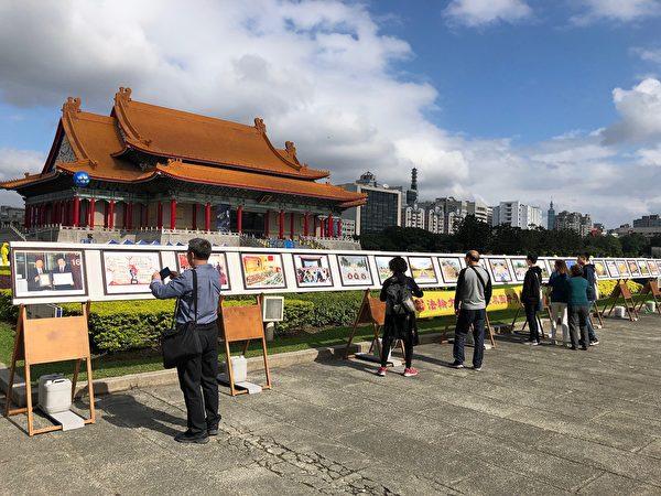 2018年11月24日,大陸遊客在台灣台北自由廣場的法輪功真相展版前了解法輪功洪傳世界與被迫害真相。(明慧網)