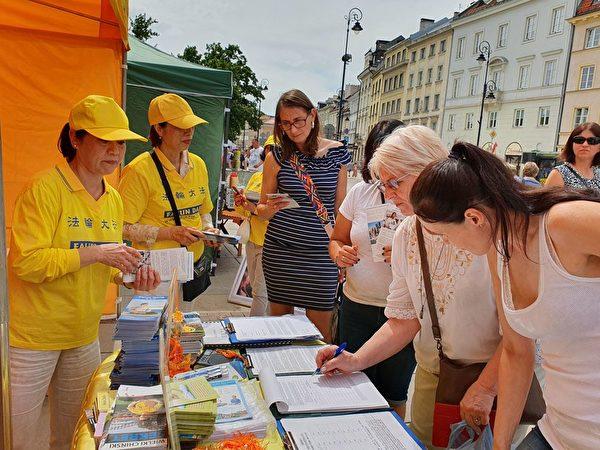 民眾在給波蘭政府的請願書上簽名。(明慧網)