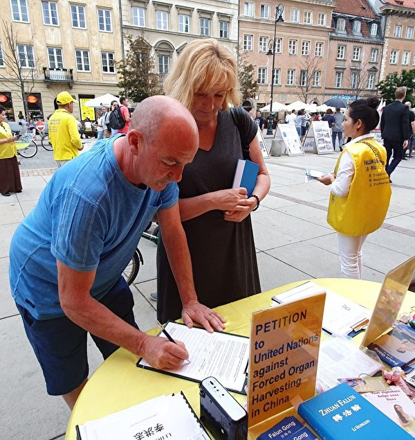 購買《轉法輪》的波蘭夫婦在請願書上簽名,反對中共迫害法輪功。(明慧網)