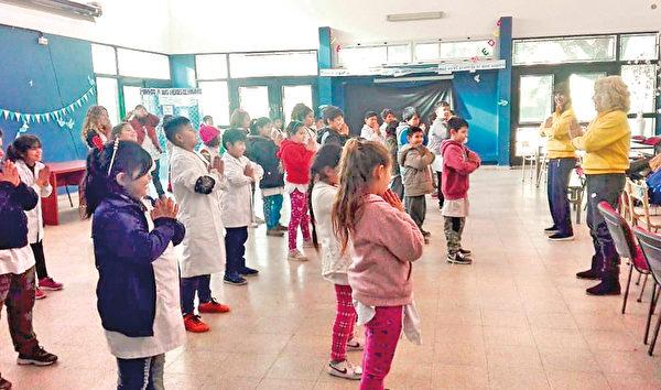 2018年,阿根廷首都的法輪功學員在索拉諾鎮一所學校教孩子煉法輪功。(明慧網)