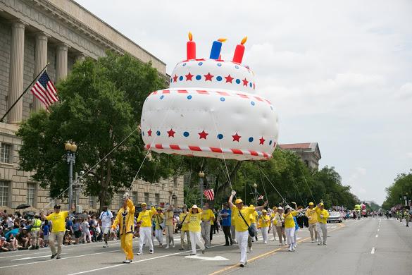 今年是美國法輪功學員連續第18年受邀參加美國獨立日大遊行,也是天國樂團連續第14年受邀。圖為法輪功隊伍手持美國生日蛋糕。(李莎/大紀元)