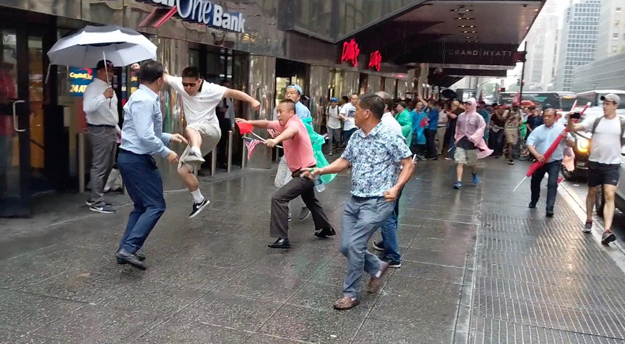 親共打手(跳起者)對歡迎蔡英文的民運人士拳打腳踢。(黃小堂/大紀元)