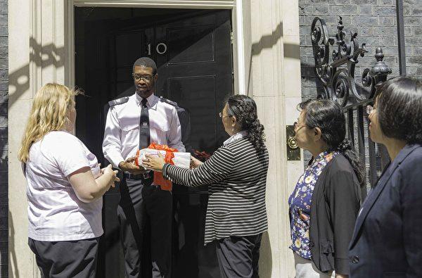 7月20日下午,英國法輪大法協會代表和幾名曾親身遭受中共迫害的先旅居英國的法輪功學員向英國唐寧街首相府工作人員轉交88688個聯名請願。(冠奇/大紀元)