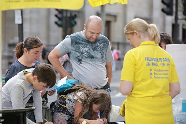 7月20日下午,很多民眾在仔細聆聽英國法輪功學員們的講解後,簽名支持法輪功學員反迫害。(冠奇/大紀元)