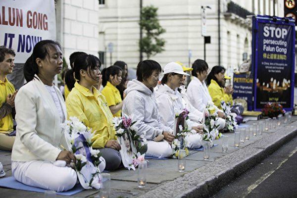 7月20日晚,英國部份法輪功學員們再次回到中領館前,進行燭光守夜活動,悼念逝去的法輪功學員們。(冠奇/大紀元)
