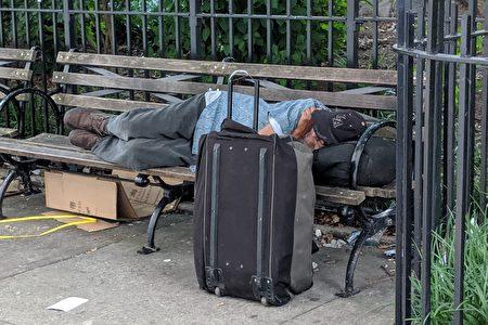 遊民攜帶全部家當睡在哥倫布公園旁的長椅上。