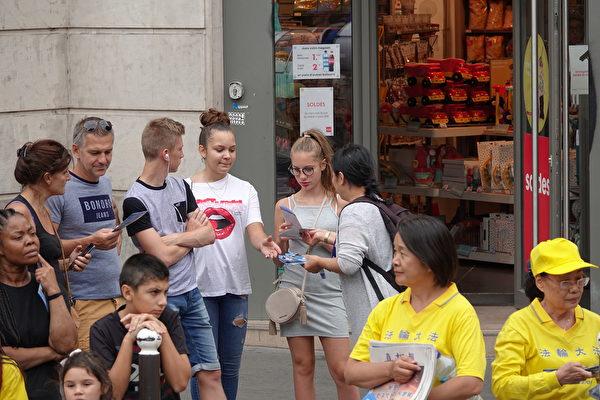 7月20日下午,來自歐洲十幾個國家的部份法輪功學員在法國巴黎舉行「紀念法輪功學員反迫害20周年」大遊行。沿途市民接過傳單,了解法輪功遭到中共迫害的真相。(葉蕭斌/大紀元)
