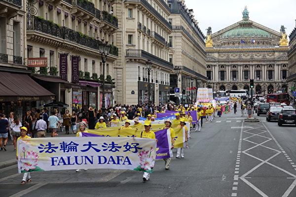 7月20日下午,來自歐洲十幾個國家的部份法輪功學員在法國巴黎舉行「紀念法輪功學員反迫害20周年」大遊行,圖為遊行隊伍途經巴黎歌劇院。(葉蕭斌/大紀元)
