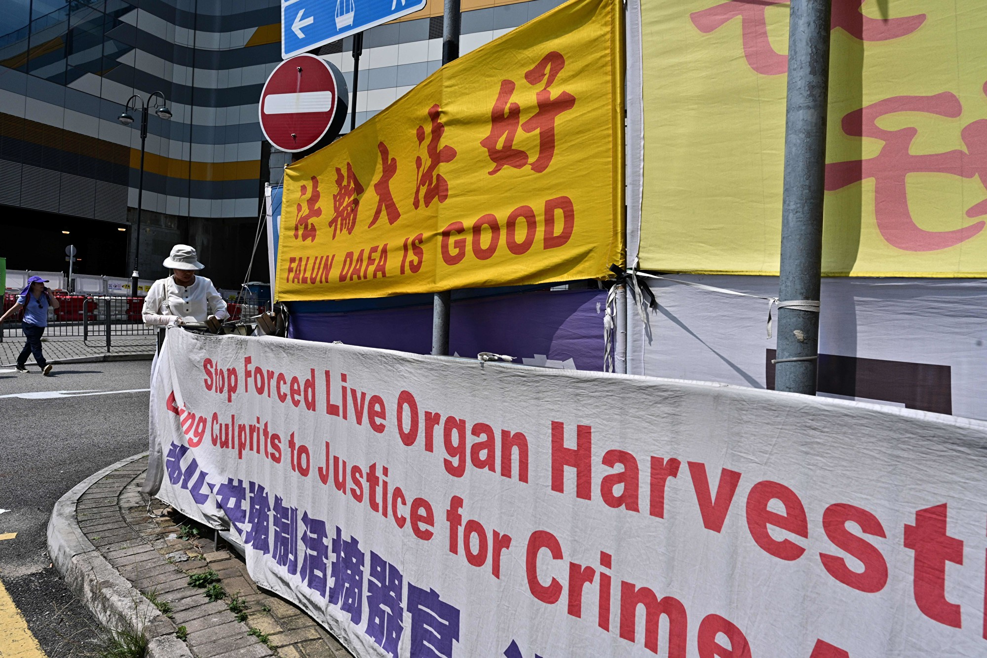 2019年4月25日,一名香港法輪功女學員在大陸遊客經常光顧的東涌調整支持法輪功的橫幅。(Anthony WALLACE/AFP/Getty Images)
