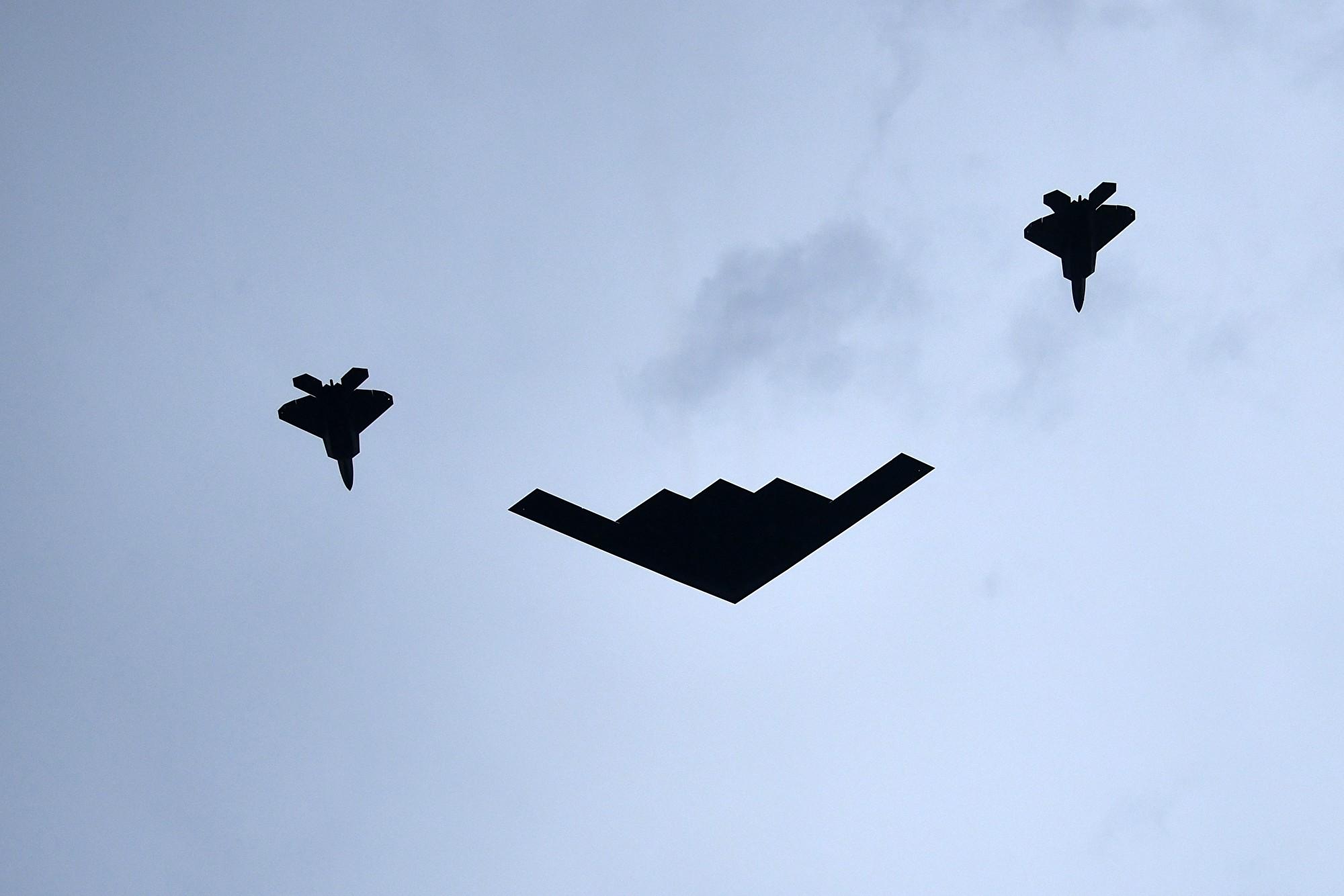 一架B-2幽靈轟炸機(中)和兩架F-22戰機飛過頭頂。(Brendan Smialowski/AFP)