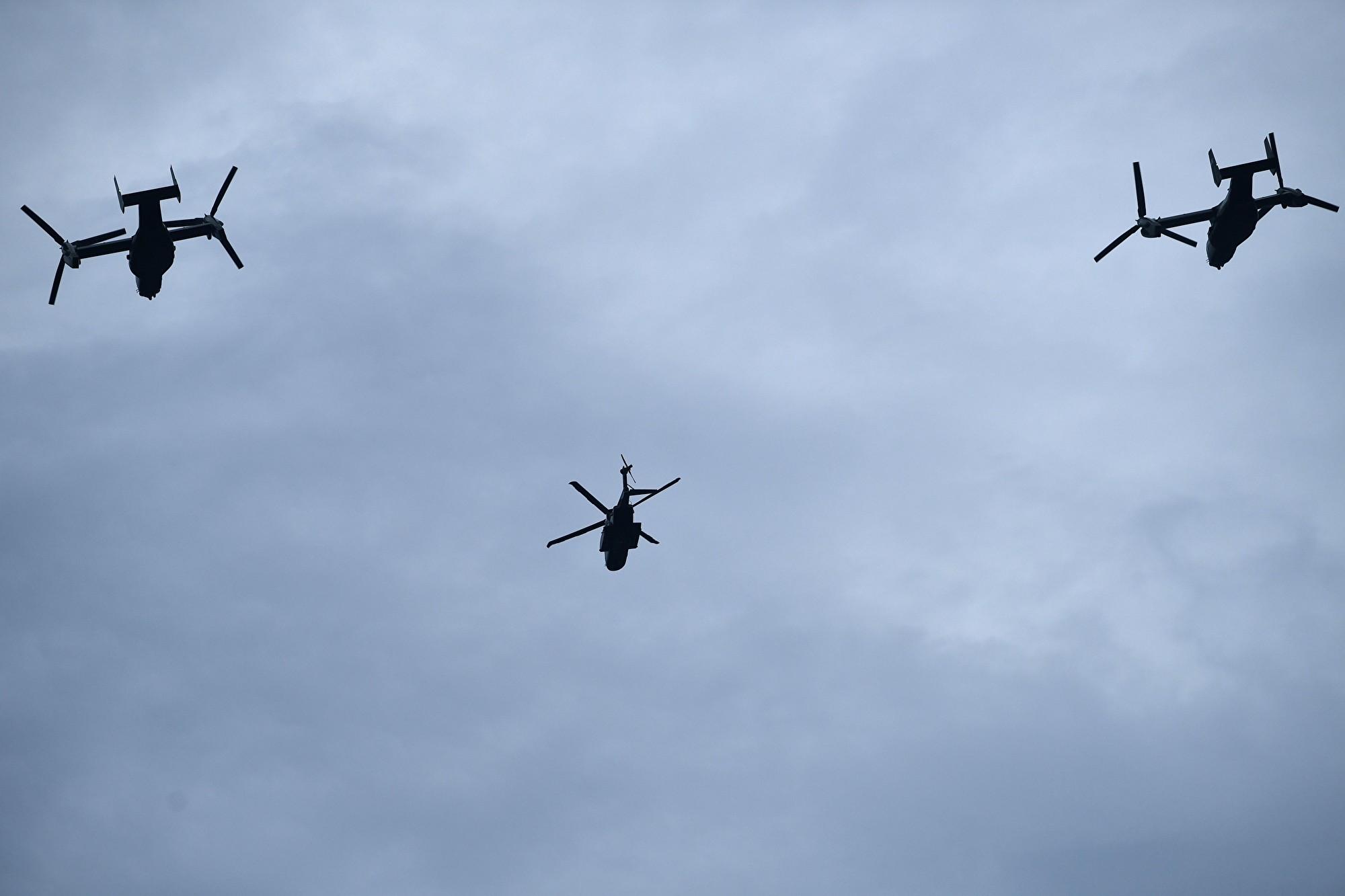一架新的海軍陸戰隊一號直升機(中)和兩架魚鷹式傾轉旋翼機飛過頭頂。 (Brendan Smialowski/ AFP)