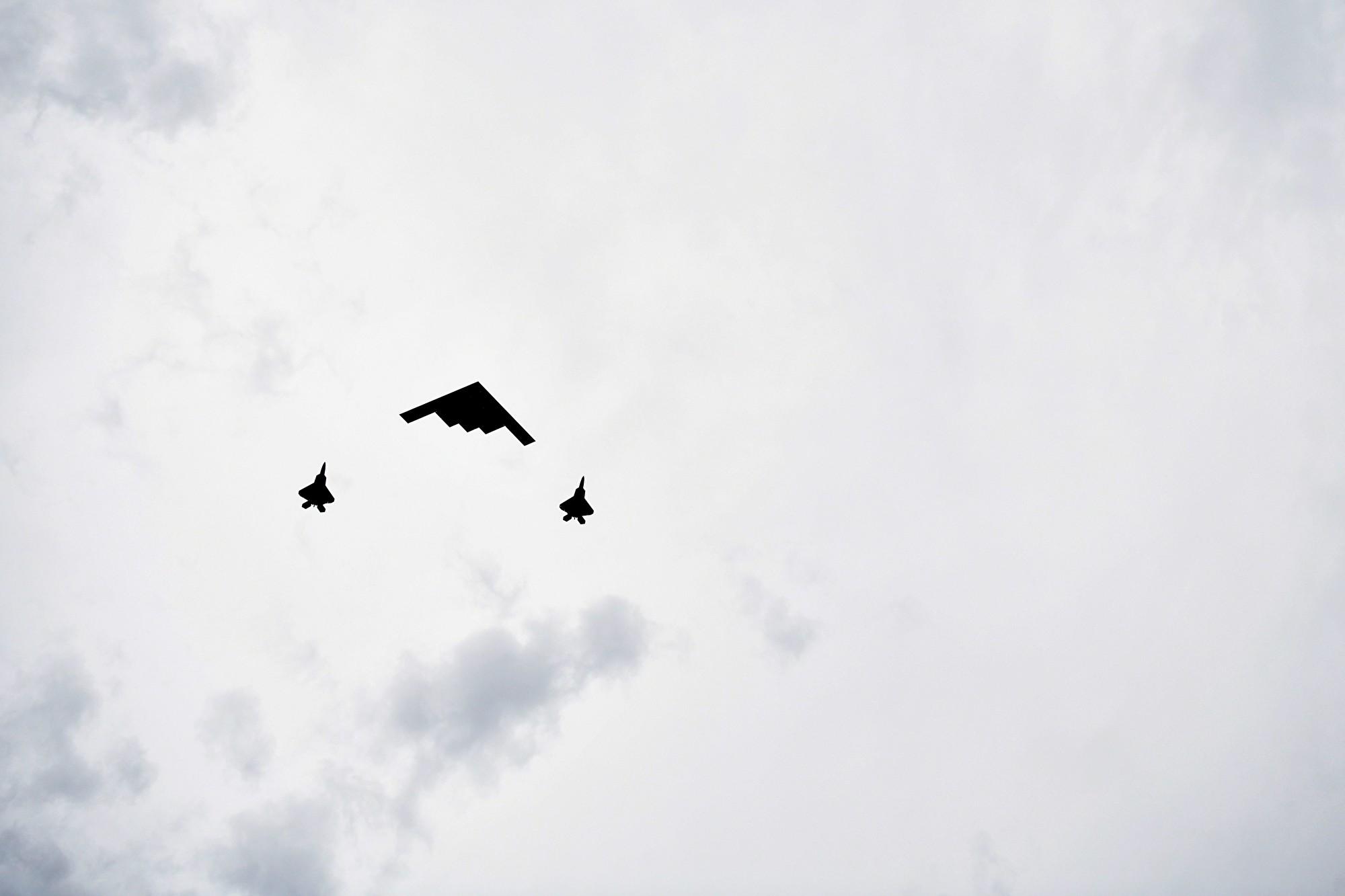 一架B-2幽靈轟炸機(中)和兩架F-22戰機飛過頭頂。 (MANDEL NGAN/AFP)