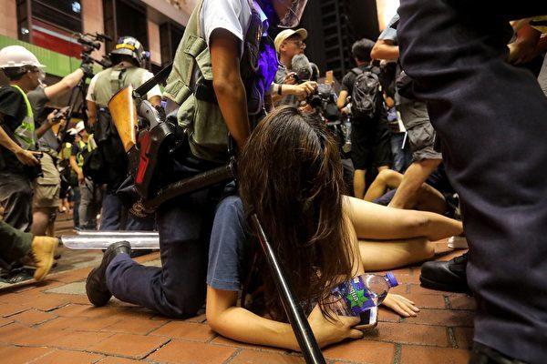 7月7日警方深夜11時前採取清場。圖為一女示威市民遭揹著長槍的警員壓倒地上。( VIVEK PRAKASH/AFP/Getty Images)
