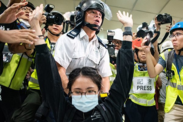TOPSHOT - A protester gestures as a policeman looks on inside a shopping arcade in Sha Tin of Hong Kong after a rally against a controversial extradition law proposal in Sha Tin district of Hong Kong on July 14, 2019. - Riot police and protesters fought running battles in a Hong Kong shopping mall on July 14 night as unrest caused by a widely loathed plan to allow extraditions to mainland China showed no sign of abating. (Photo by Philip FONG / AFP) (Photo credit should read