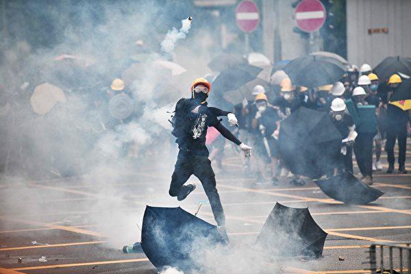 7月27日,反黑反送中的民眾不顧警察反對,成千上萬的民眾來到元朗。圖為一青年把警察發射的催淚彈扔回去。(