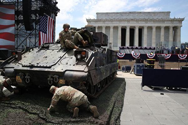 為了防止M1艾布拉姆斯坦克壓壞路面,軍人們正在鋪墊保護物。(Mark Wilson/Getty Images)
