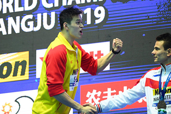 英國選手斯科特‧鄧肯拒絕與獲得金牌的孫楊(左)握手、合照,孫楊在同身邊俄羅斯選手馬尤丁握手之際,對著遠處的鄧肯怒吼。(Quinn Rooney/Getty Images)