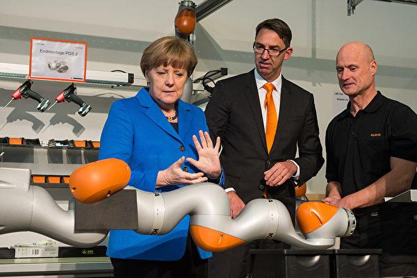 圖為2015年3月13日,「庫卡」CEO羅伊特(Till Reuter,中)陪同德國總理默克爾造訪設在德國奧格斯堡的庫卡工業機械人生產工廠。(Joerg Koch/Getty Images)