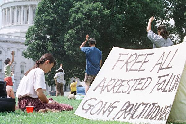 1999年7月27日,部份美國法輪功學員在國會前煉功,手寫標語「釋放所有被捕法輪功學員」。(Alex Wong/Getty Images)
