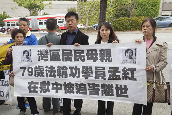 李雪松(右二)與其他法輪功學員,在三藩市中領館前手持剛剛貼上母親遺像的橫幅。(周鳳臨/大紀元)