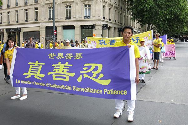 遊行隊伍中,手舉「世界需要真、善、忍」橫幅的法輪功學員王喆(右)。(關宇寧/大紀元)