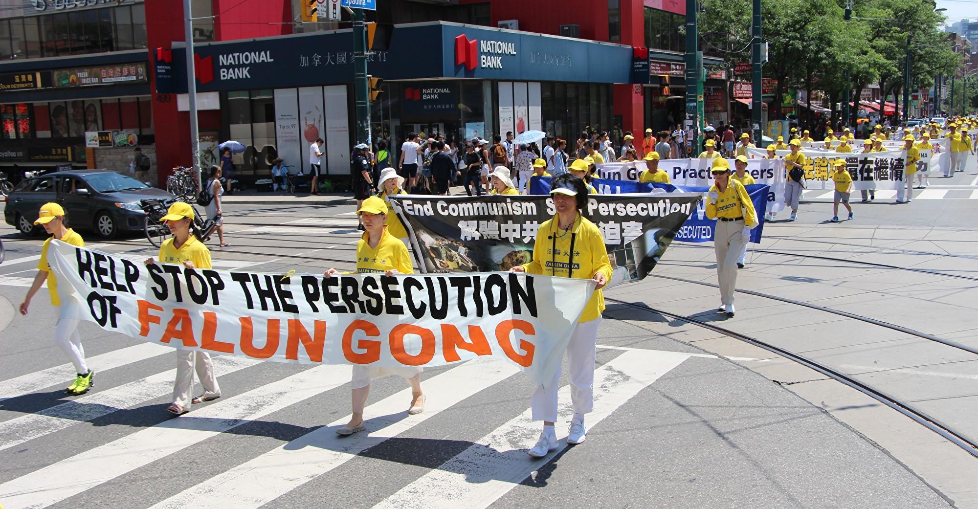7月20日,加東地區法輪功學員舉行盛大遊行,紀念反迫害20周年,圖為學員手拿橫幅「幫助停止迫害法輪功。(Jimmy Pizolinas/大紀元)