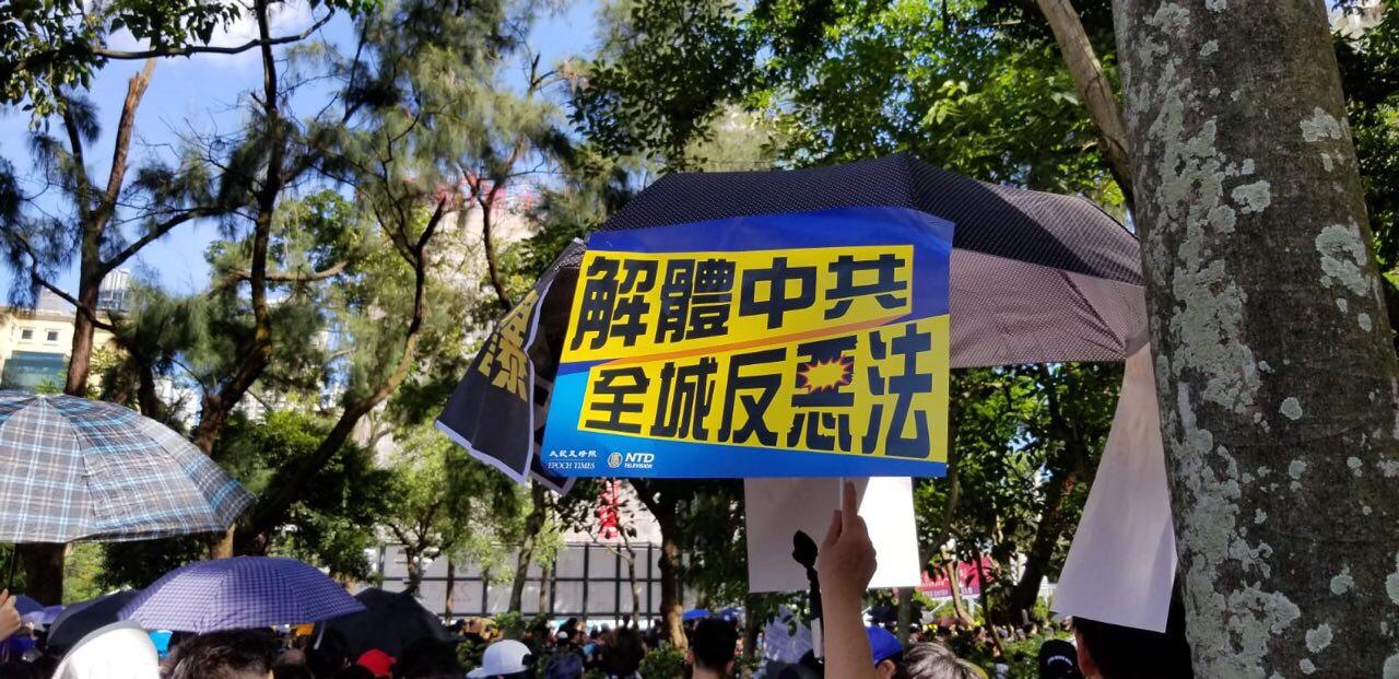 2019年7月1日,香港,民眾手持「解體中共 全城反惡法」的標語參加遊行表達不滿。港府強推《逃犯條例》修訂草案後引發民怨,民眾走上街頭抗議,要求撤回惡法。(大紀元)
