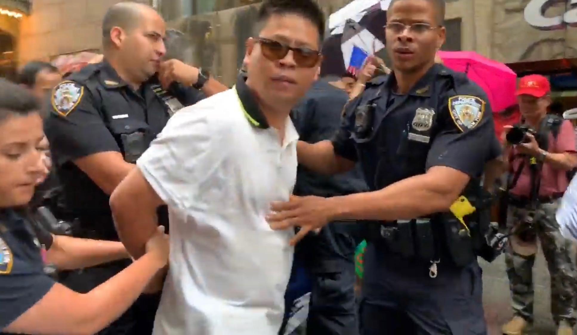對民運人士拳打腳踢的親共分子,被警方拘捕。(林丹/大紀元)