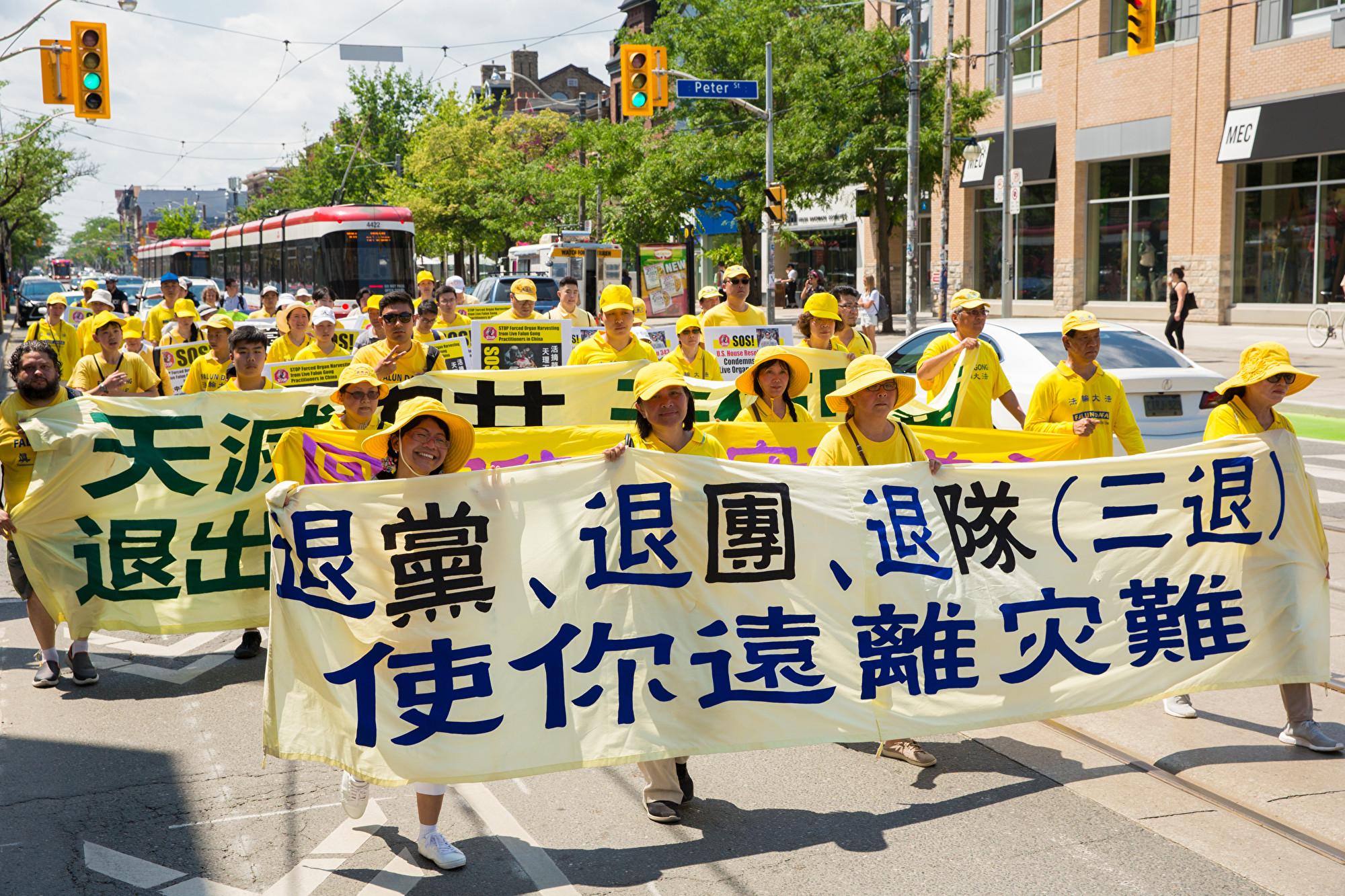 7月20日,加東地區法輪功學員舉行盛大遊行,紀念反迫害20周年,圖為學員手拿橫幅「退黨、退團、退隊(三退),使你遠離災難。(艾文/大紀元)