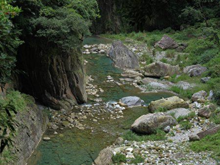 砂卡礑溪緩緩注入立霧溪中的匯口,堆疊的大小巨石中,湧現出清澈見底的湛藍溪水。