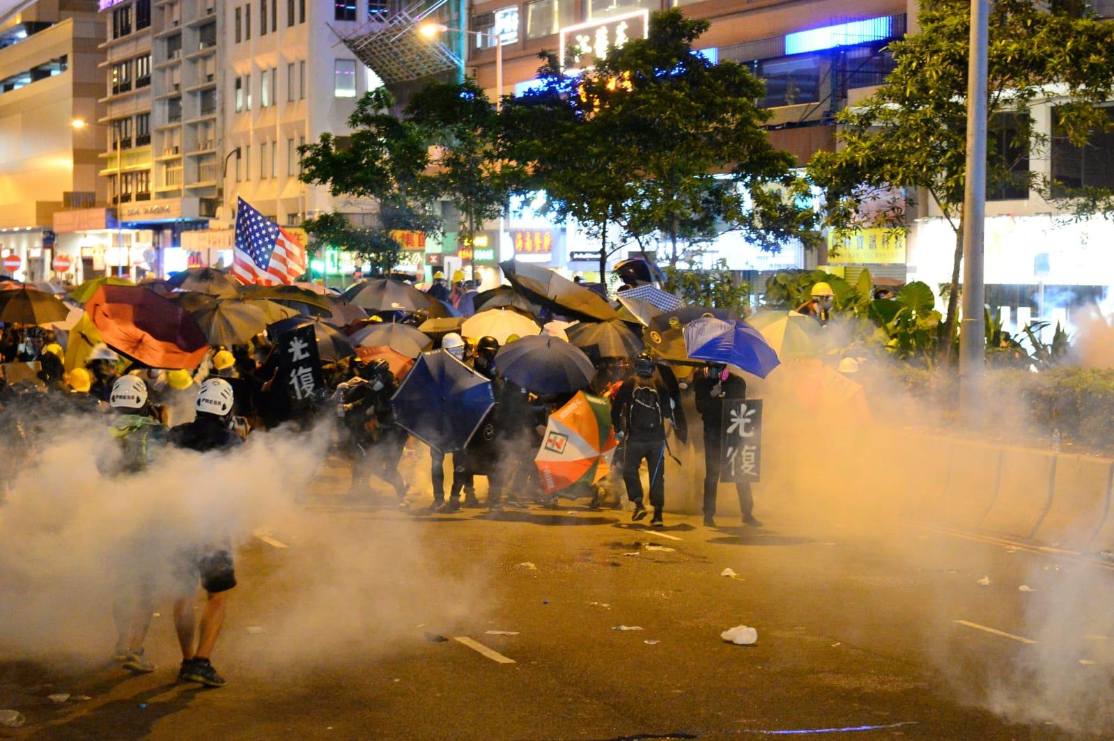 2019年7月28日,香港,面對警察頻繁發射橡膠子彈及催淚彈清場,許多香港民眾戴上口罩與頭盔,並以雨傘抵抗。(宋碧龍/大紀元)