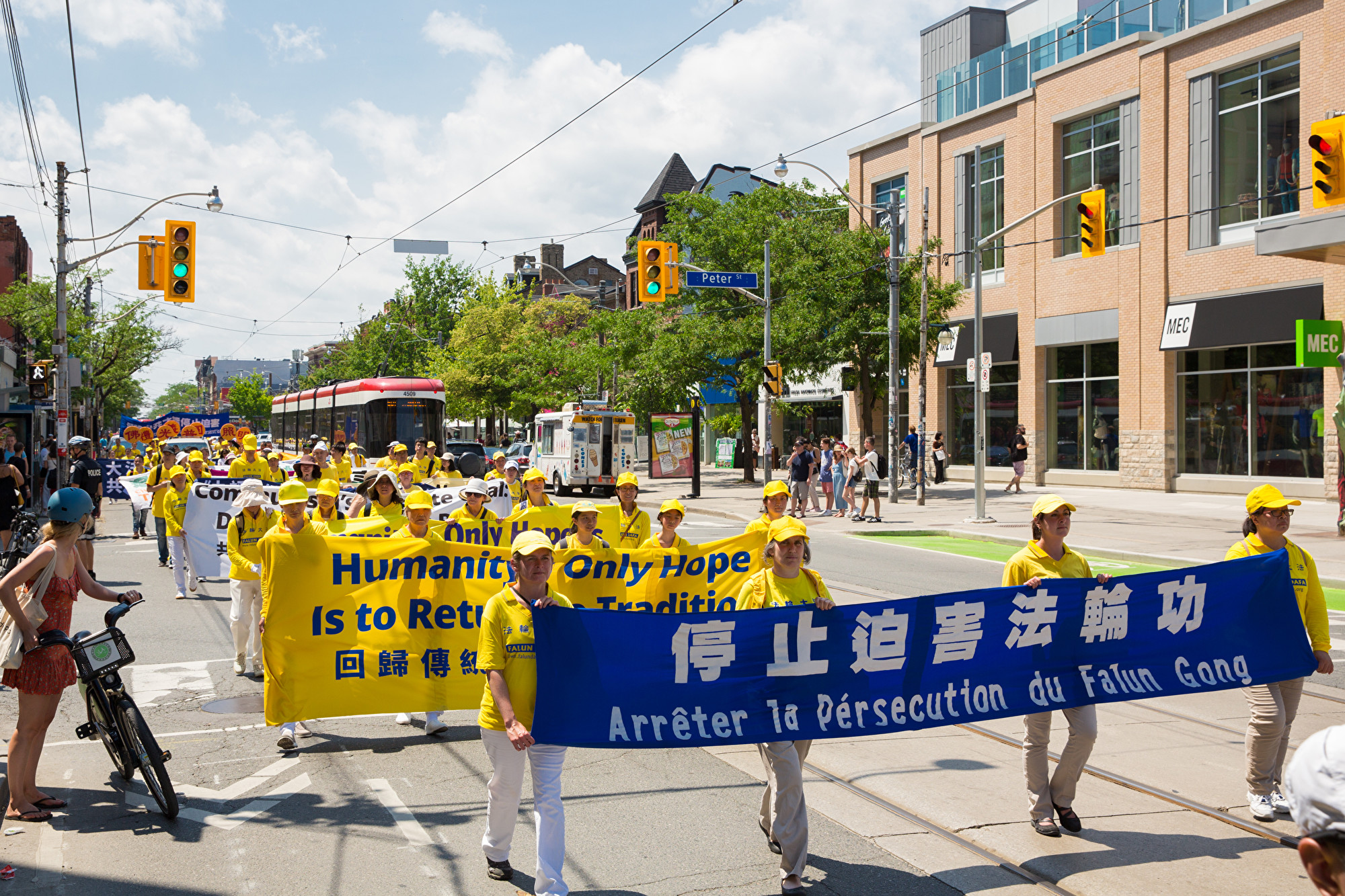 7月20日,加東地區法輪功學員舉行盛大遊行,紀念反迫害20周年,圖為學員手拿橫幅「停止迫害法輪功。(艾文/大紀元)