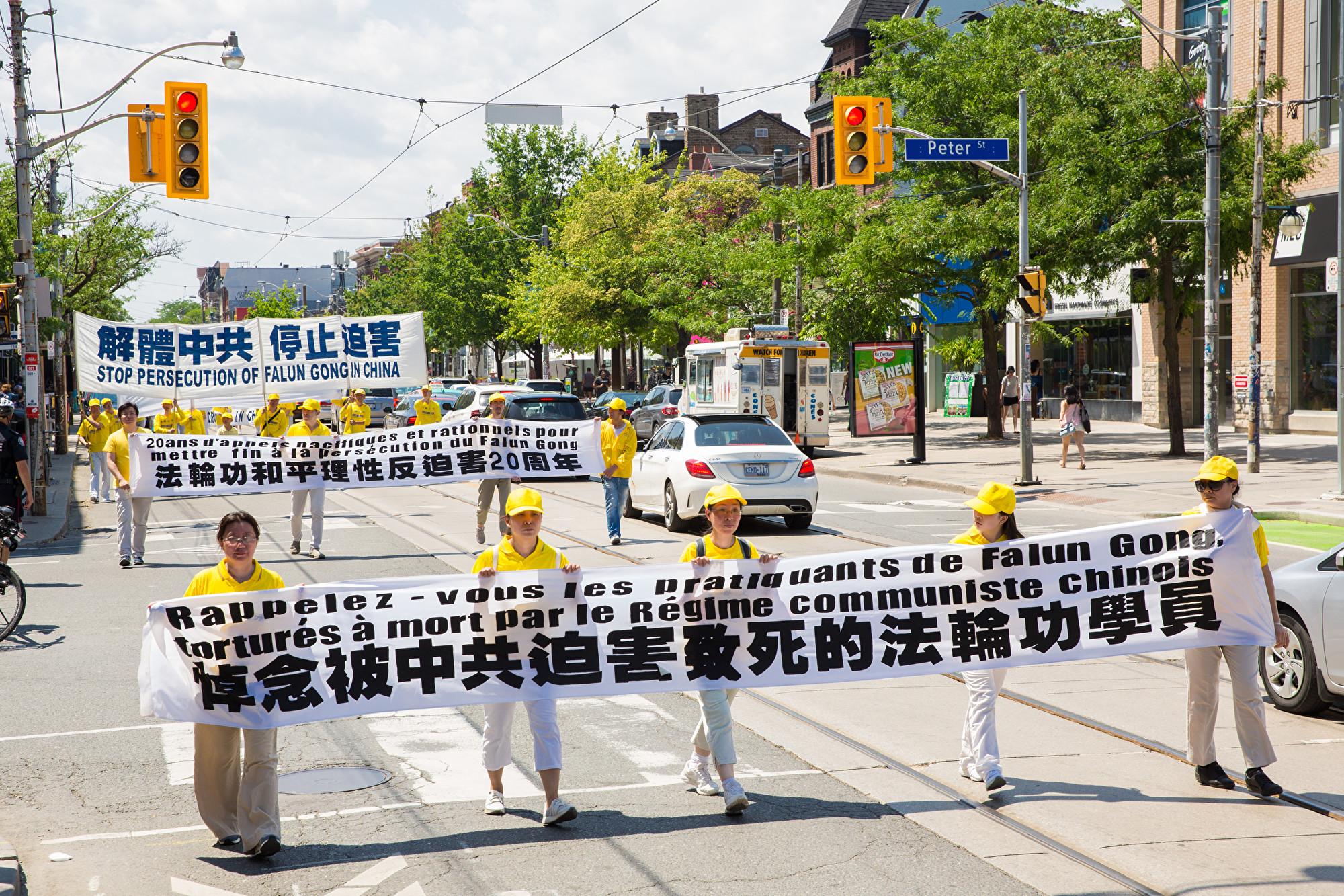 7月20日,加東地區法輪功學員舉行盛大遊行,紀念反迫害20周年,圖為學員手拿橫幅「悼念被中共迫害致死的法輪功學員。(艾文/大紀元)