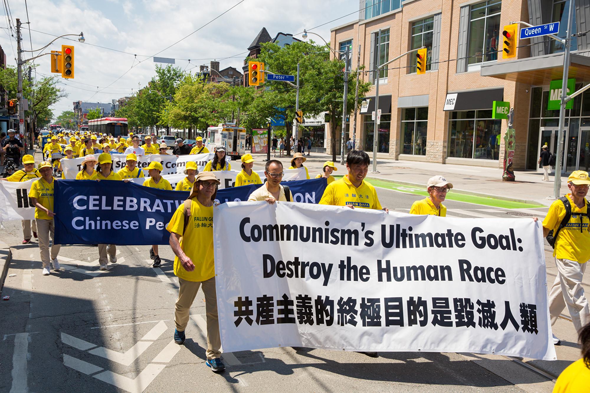 7月20日,加東地區法輪功學員舉行盛大遊行,紀念反迫害20周年,圖為學員手拿橫幅「共產主義的終極目的是毀滅人類。(艾文/大紀元)