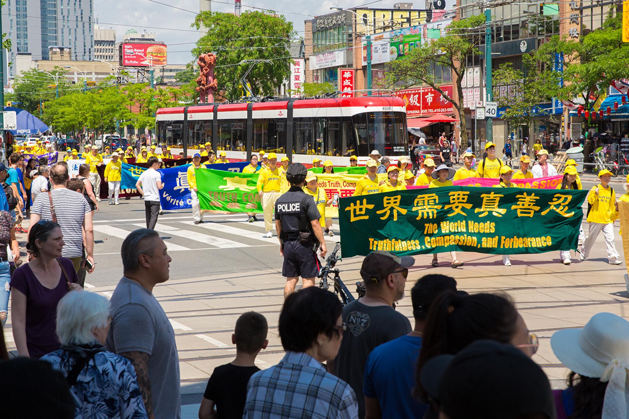 7月20日,加東地區法輪功學員舉行盛大遊行,紀念反迫害20周年,圖為學員手拿橫幅「世界需要真、善、忍」。(艾文/大紀元)