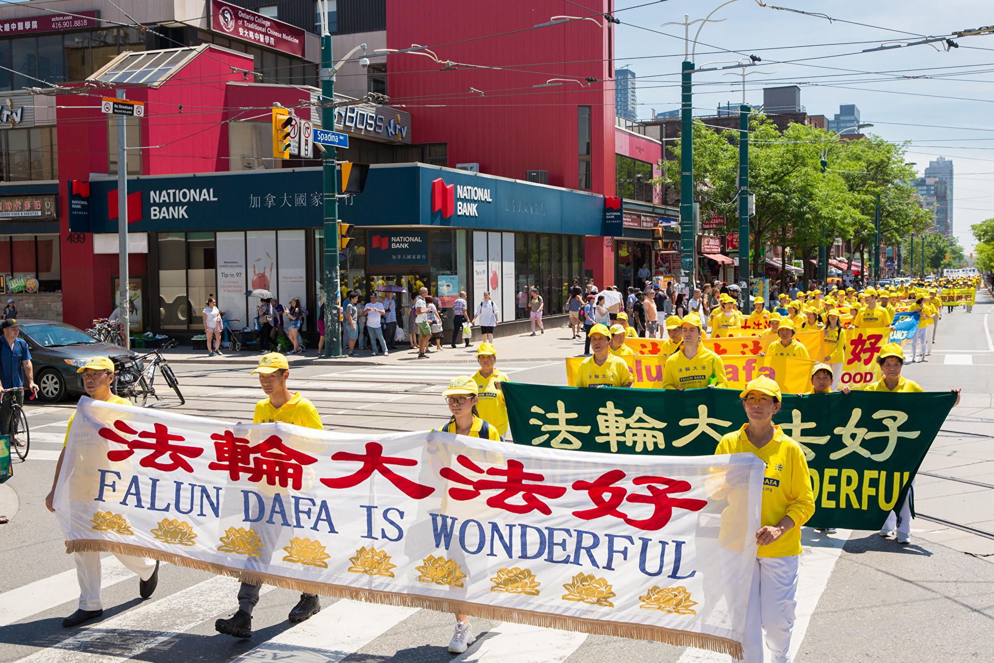 7月20日,加東地區法輪功學員舉行盛大遊行,紀念反迫害20周年,圖為學員手拿橫幅「法輪大法好。(艾文/大紀元)