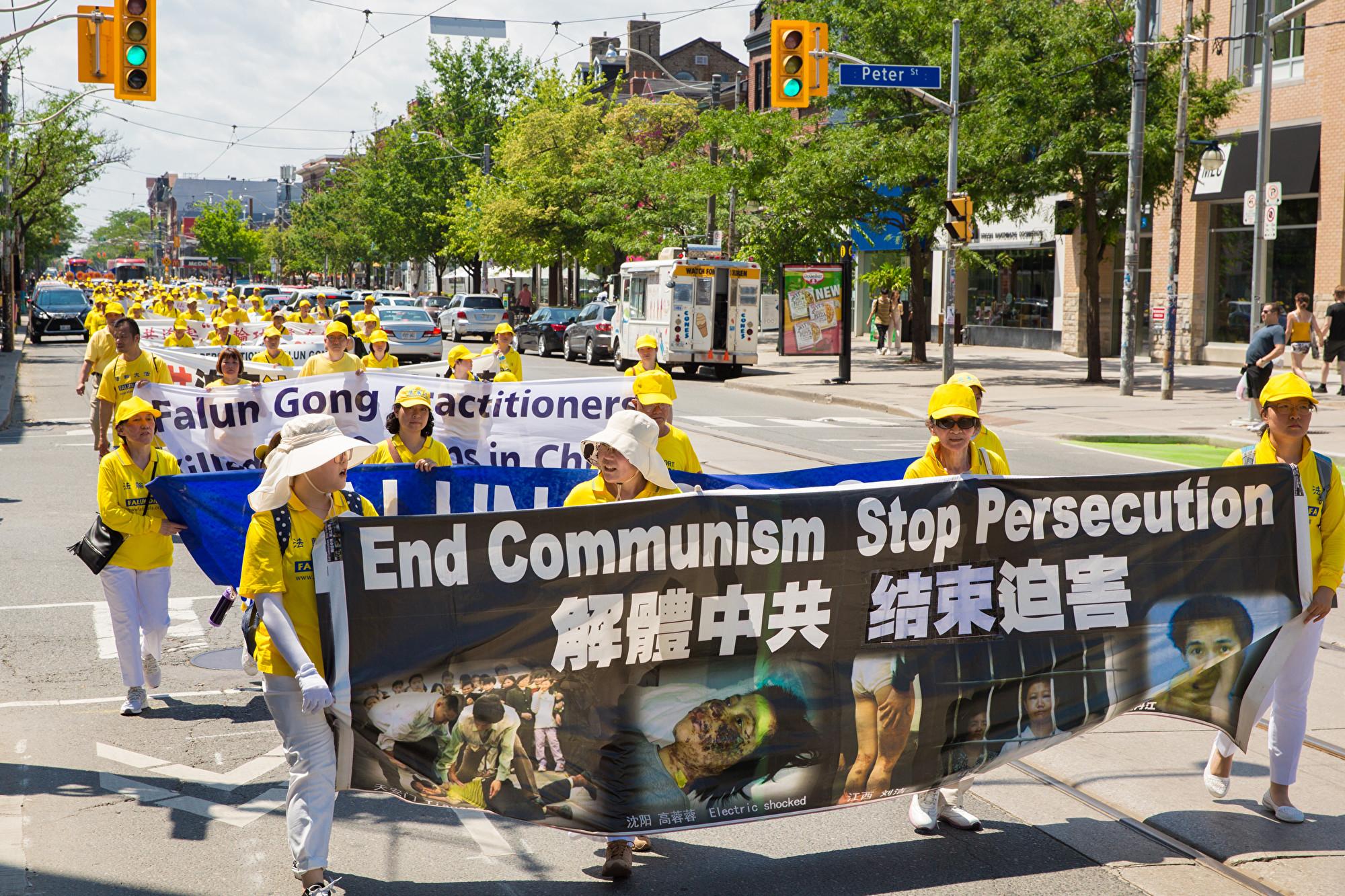 7月20日,加東地區法輪功學員舉行盛大遊行,紀念反迫害20周年,圖為學員手拿橫幅「解體中共,結束迫害。(艾文/大紀元)