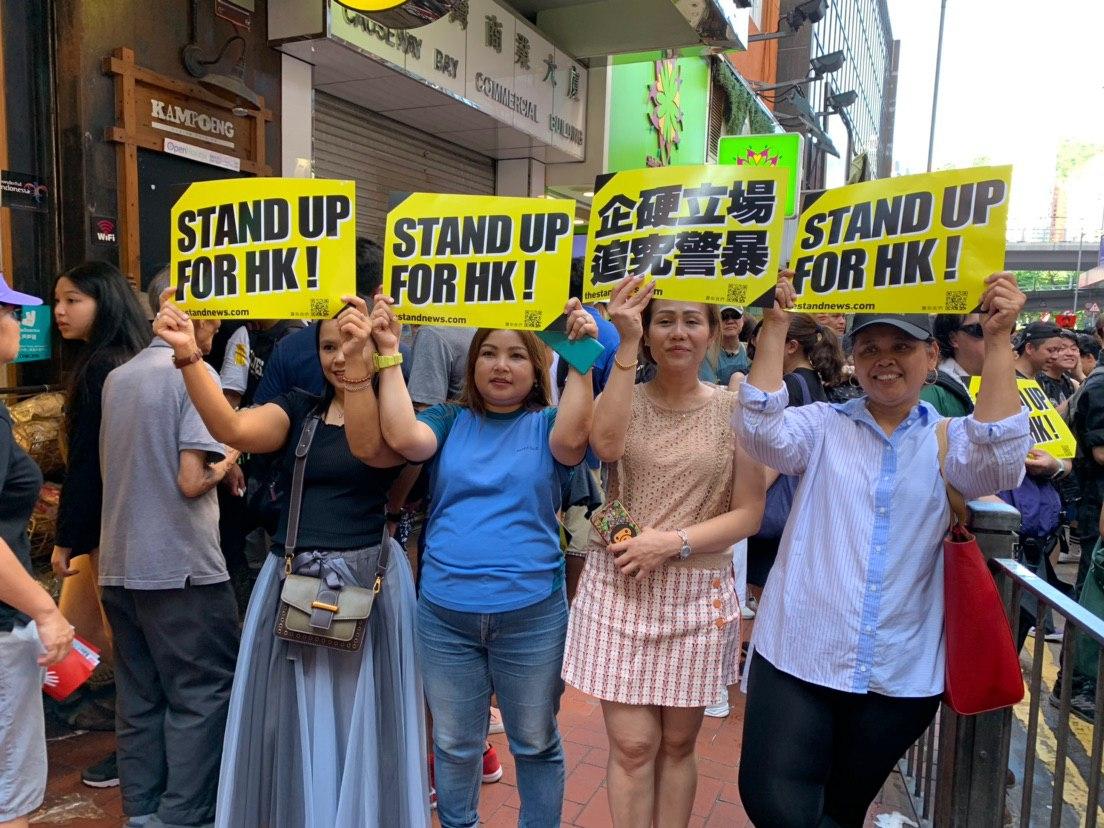 長年生活在香港的馬來西亞人,她們在自己工作的餐廳前的人行道上打出支持的標語。(駱亞/大紀元)