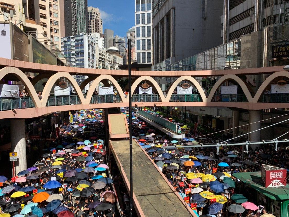 大陸青年在銅鑼灣站在圓形天橋上觀看遊行隊伍。(駱亞/大紀元)