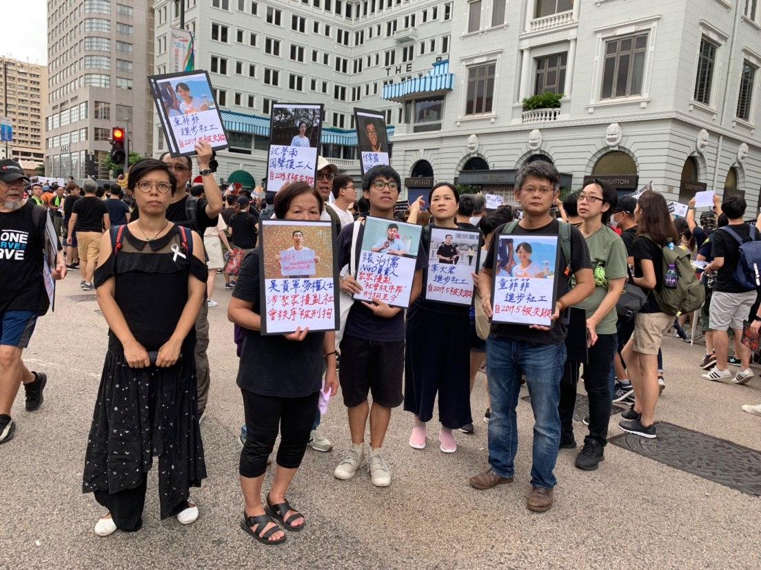 7.7大遊行的中途香港工黨創黨的前主席胡惠姍(左一)跟一班人手舉展板揭露中共迫害社工、異見人士等。(駱亞/大紀元)
