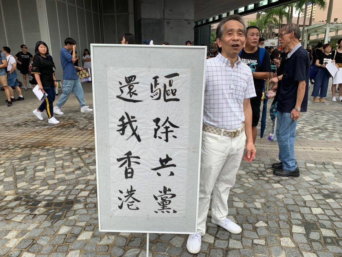 現場香港老人打出展板「驅除共黨,還我香港」(駱亞/大紀元)