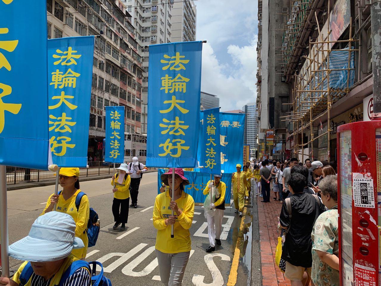 7月21日香港法輪功學員舉行反迫害二十周年遊行集會,引起路人駐足觀看。(駱亞/大紀元)