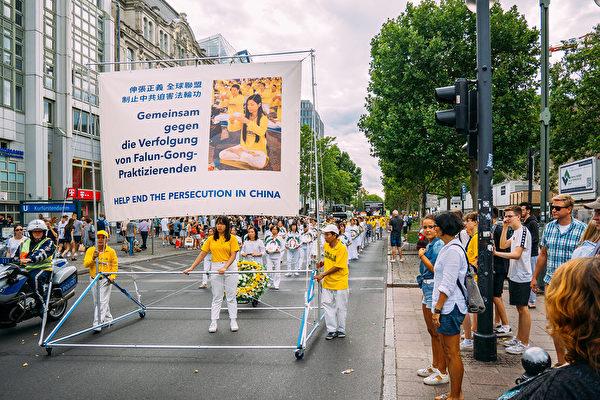 8月10日下午,法輪功遊行隊伍經過西柏林中心歐洲廣場,眾多路人駐足觀看。(張清颻/大紀元)