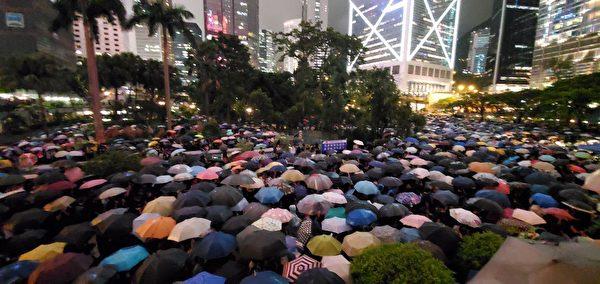 公務員集會參加者逼滿遮打花園,人潮延至對面馬路。很多議員發言。現場下大雨,人們撐起傘。(宋碧龍/大紀元)