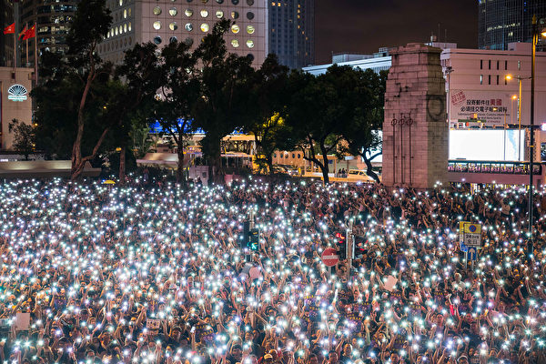 公務員集會9時許結束,發起人在台上呼籲參加者和平散去。人們舉起手機,點點星光照亮遮打花園。(Billy H.C. Kwok/Getty Images)