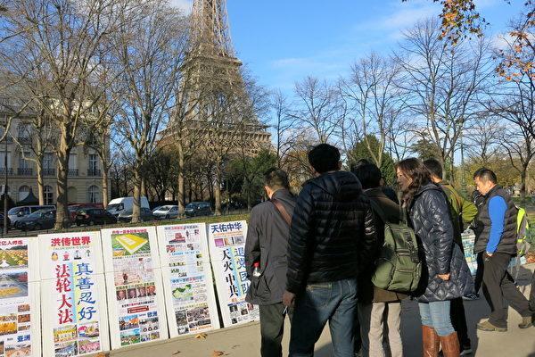 大陸遊客在巴黎艾菲爾鐵塔景點上觀看法輪功真相展板。(大紀元)